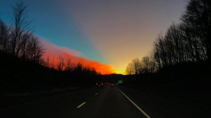 Sunset sky over I-80 with trees on either side of road.