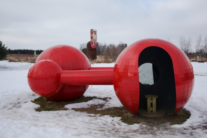 Metal sculpture with two large spheres and two smaller spheres, connected by pipes.