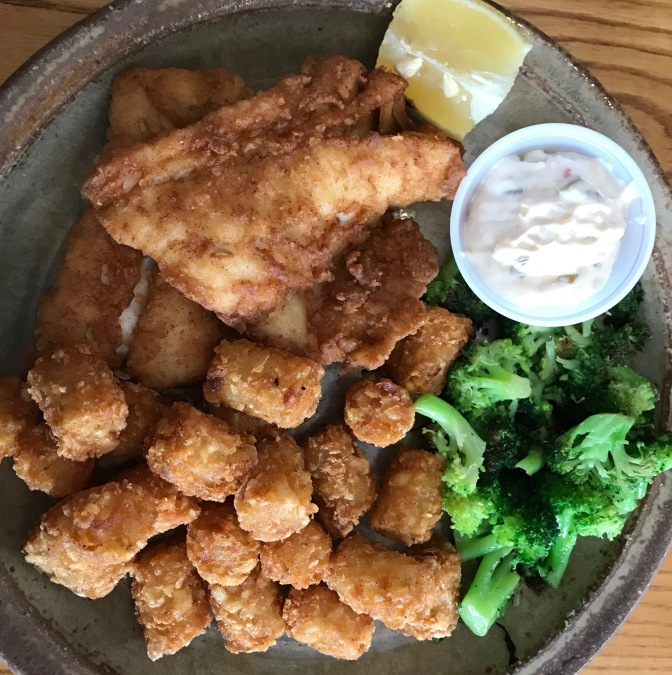 Plate with fried cod, tater tots, broccoli, and tartar sauce.