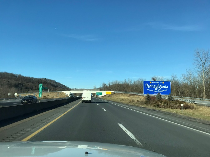 View of I-80 with blue welcome sign for Pennsylvania on right side of road.