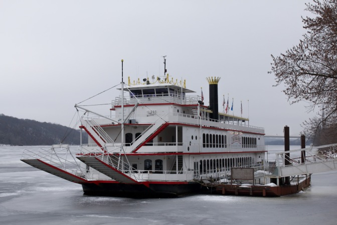 River steamboat docked along side of ice-covered St. Croix River.
