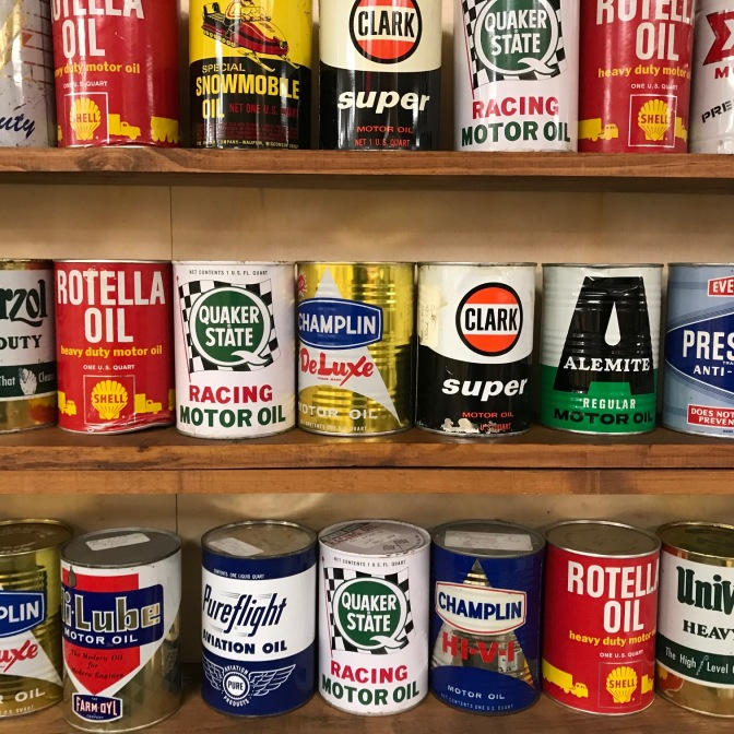 Three shelves of oil cans including Quaker State, Rotella, Clark, and Champlain.