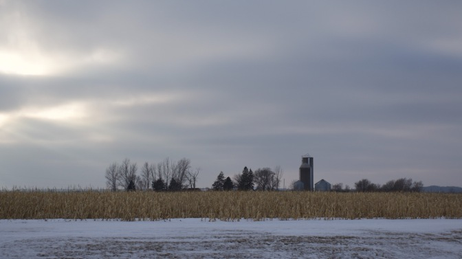 Farm silo in distance past cornfield, with the sun beginning to emerge from beneath the clouds.