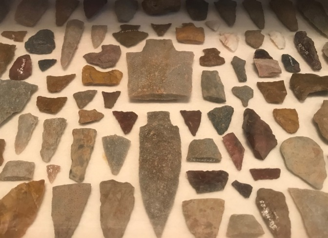 Stone arrowheads and tools in display case.