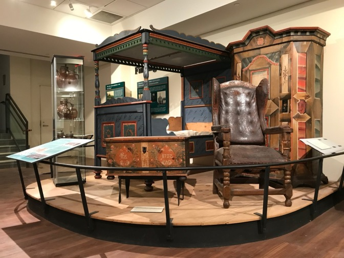 Museum display of bedroom furniture including a four poster-bed, a chest, a chair, and an armoir.