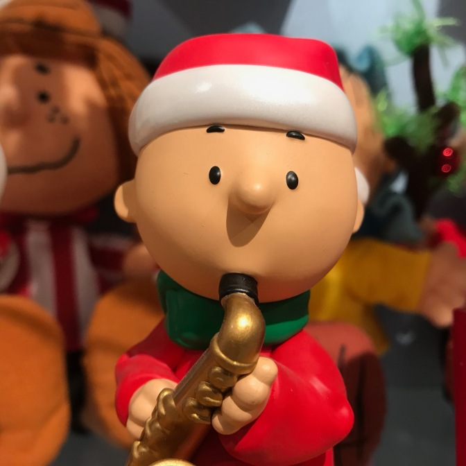 Charlie Brown figurine, dressed in a Santa outfit, playing a saxophone.