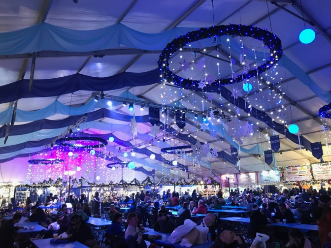 Interior of one of the main tents of the Christmas Market, with people seated at tables in foreground, shops in the background, and snowflake chandeliers hanging from ceiling.