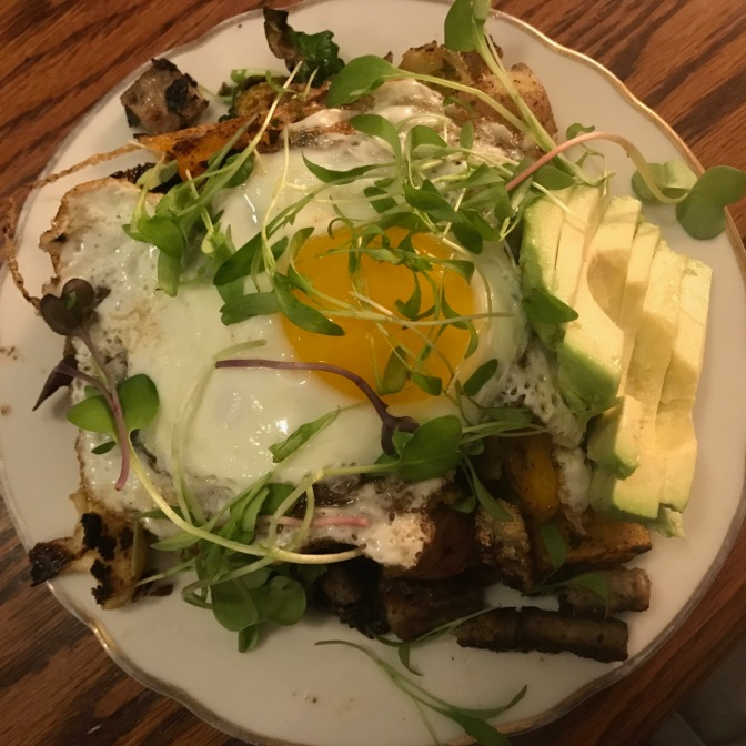 Plate of avocado, sausage, egg, greens.