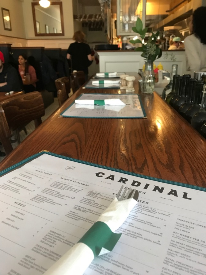 Menu and countertop of bar at Cardinal restaurant. Booths and open air kitchen are in the background.