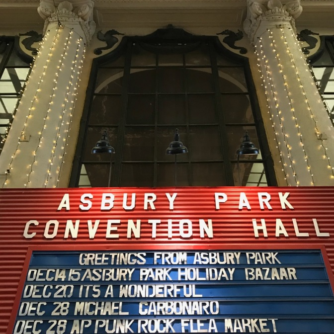 Billboard inside convention center that says ASBURY PARK CONVENTION HALL GREETINGS FROM ASBURY PARK DEC 14 15 ASBURY PARK HOLIDAY BAZAAR.