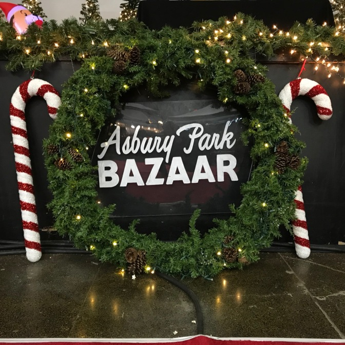 Wreath with candy canes on either side and in middle, words that say ASBURY PARK BAZAAR.