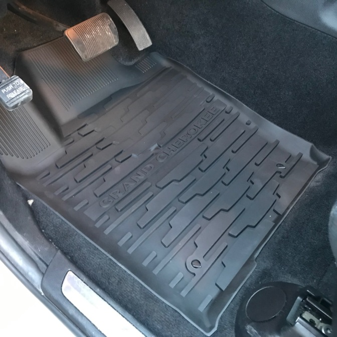Black all-weather floor mat in driver's side that says GRAND CHEROKEE.