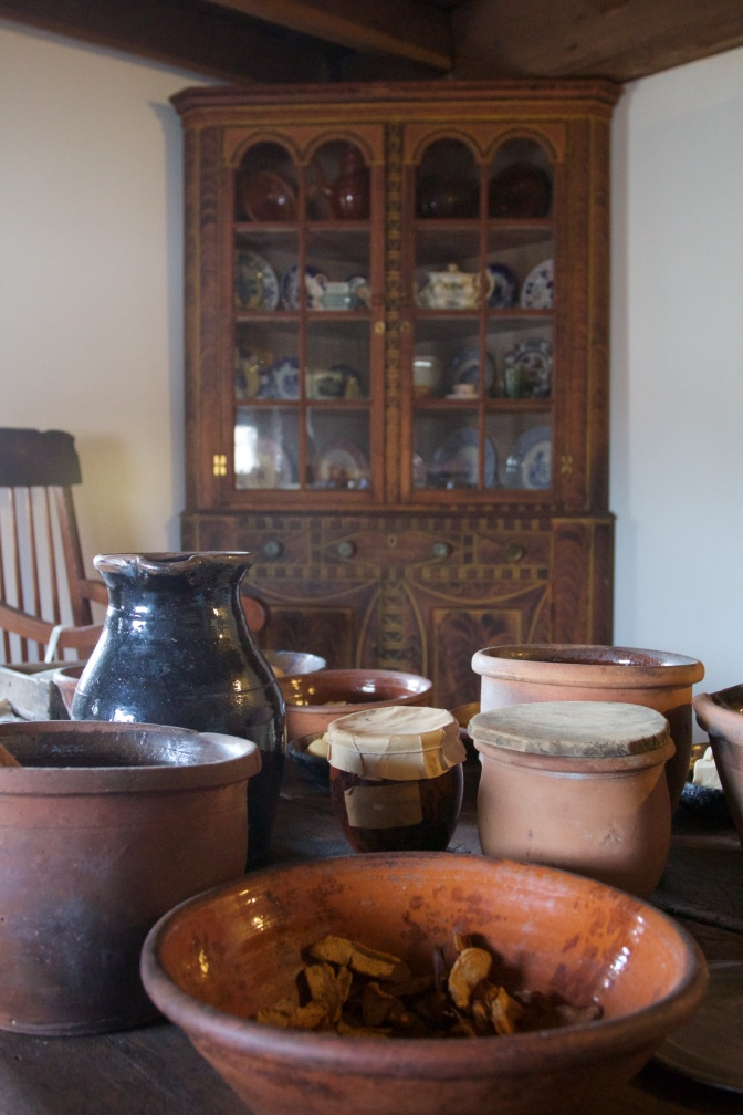 Table with cooking jars and bowls, with a corner cabinet in background.