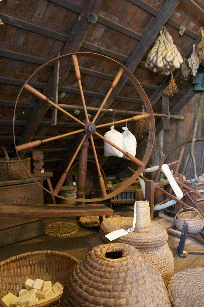 Spinner's wheel set among baskets and boxes.
