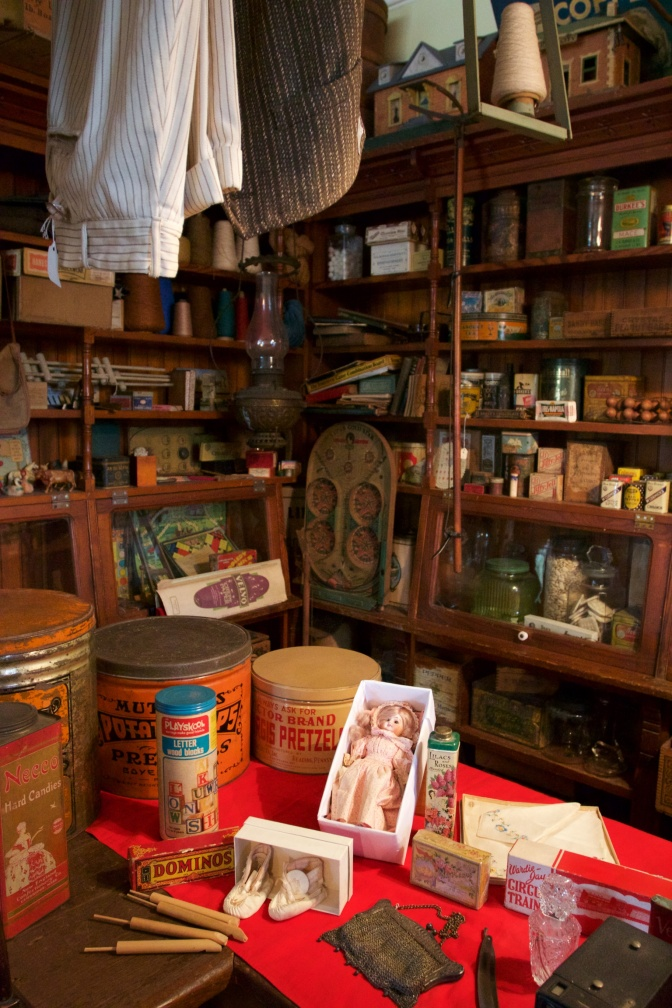 Shelves and counter of general store, with items such as cans, jars, dolls, and toys.