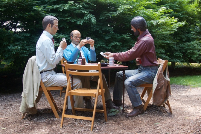 Statue of three men playing cards around card table, with a fourth chair empty.