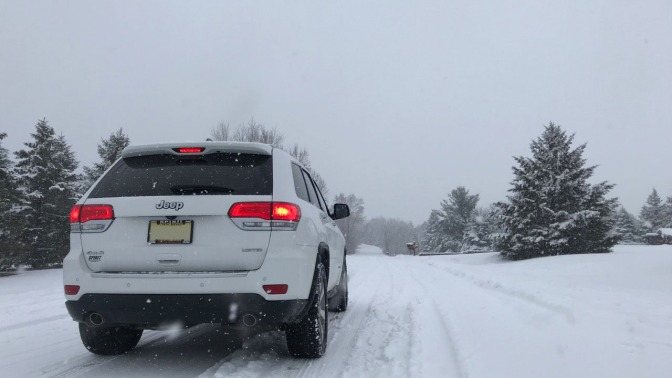 White Jeep Grand Cherokee, parked on snow-covered road.
