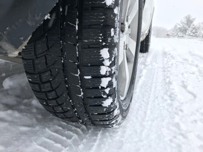 Rear wheel of Jeep and Nokian WR G4 tires, on snowy road.