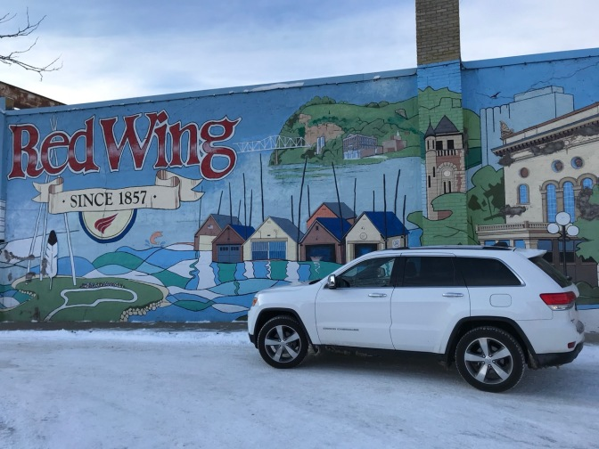 White Jeep Grand Cherokee in front of building mural of town, with a sign that says RED WING SINCE 1857