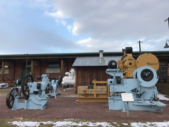 Machinery of ship building on display in plaza beside museum.