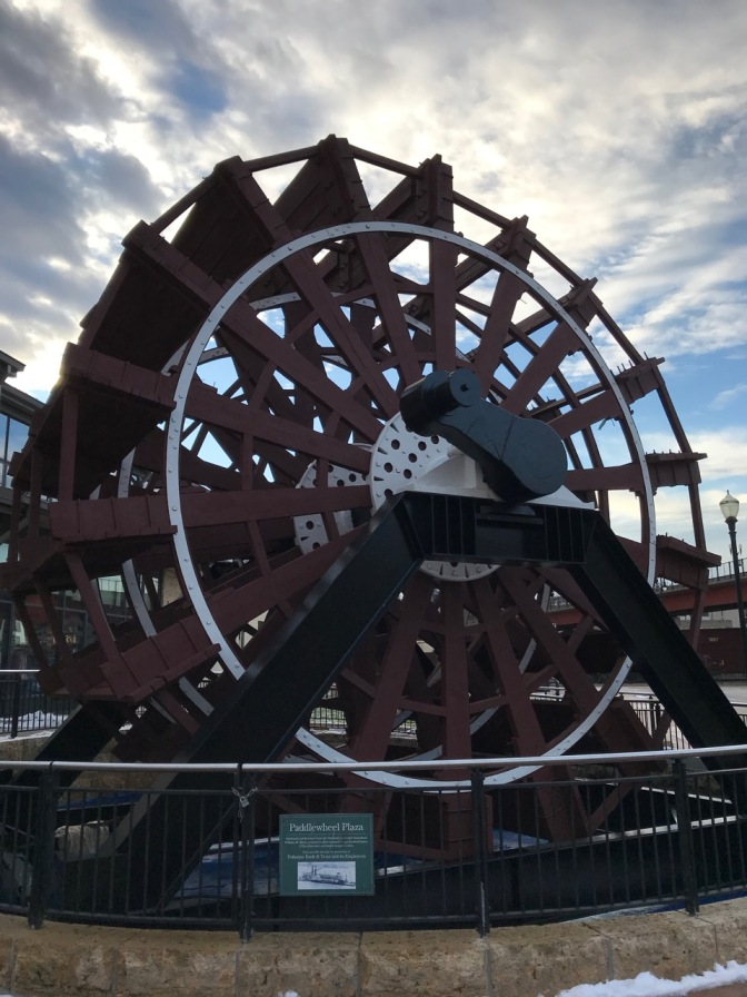 Paddlewheel on display in plaza.