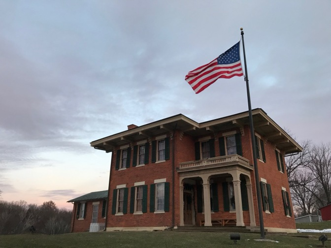 House of President Ulysses S. Grant, a two-story brick home, with a large American flag flying from a flag pole in front of the house.