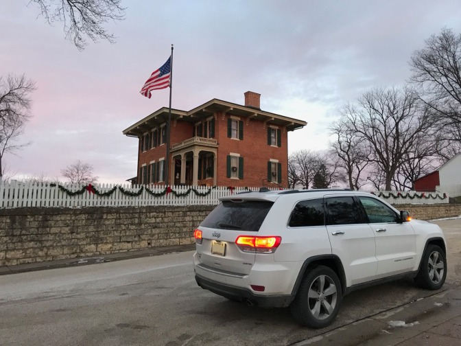White Jeep Grand Cherokee parked in front of brick house, with a large American flag flying in the distance.