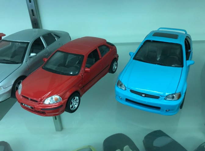 Two Honda Civic die cast toy cars, on in red and one in blue.