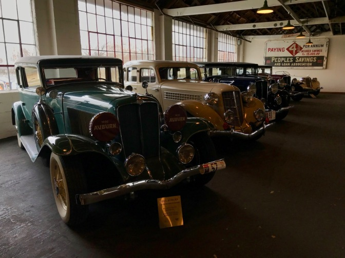 Line of five Auburn and Cord automobiles.