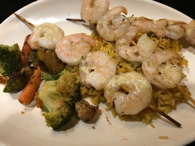 Shrimp on skewers with rice and mixed vegetables, on white plate.