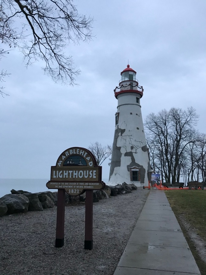 Marblehead Lighthouse with sign in front that says MARBLEHEAD LIGHTHOUSE 1821