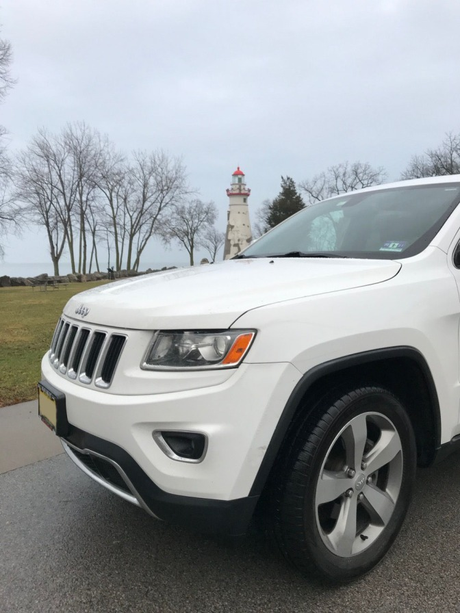 White Jeep Grand Cherokee in front of Lighthouse.