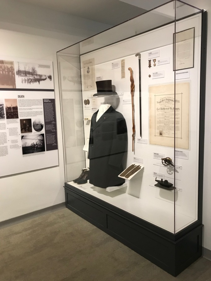 Glass display case with black coat, top hat, gloves, cane, and other personal effects of Rutherford B. Hayes.