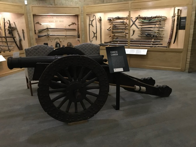 Large Chinese cannon in room filled with guns and swords.