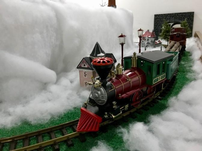 Model train running through snowy landscape.