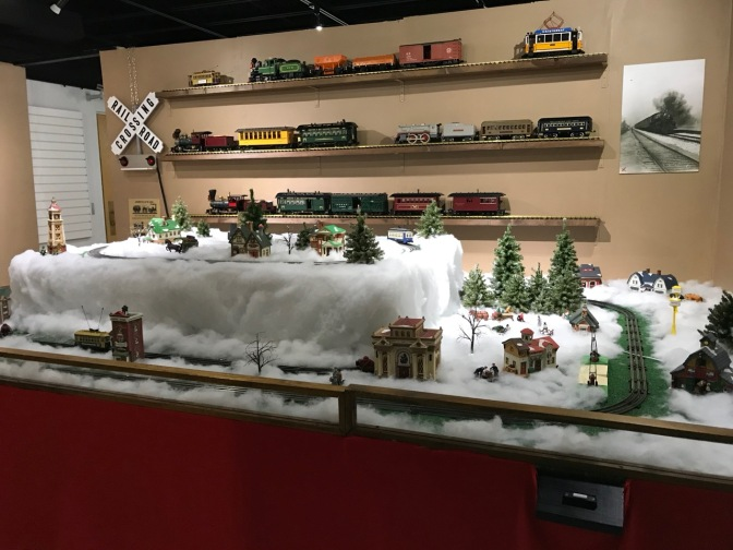 Room filled with a table with a model train set, and model trains on the walls.