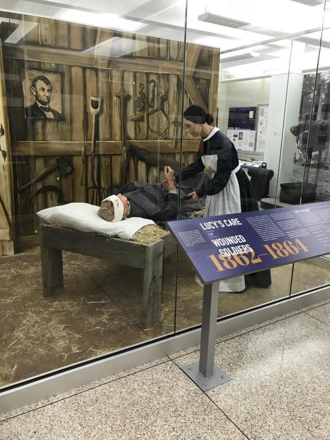 Mannequins of Civil War nurse and wounded soldier, behind a glass display case.