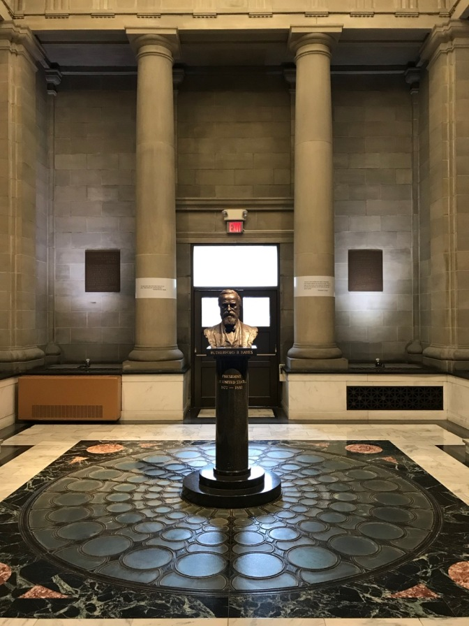 Stone and marble atrium, with bust of President Hayes in middle of room.