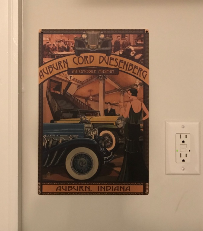 Plaque with picture of classic cars, sign says AUBURN CORD DUESENBERG AUTOMOBILE MUSEUM AUBURN INDIANA.