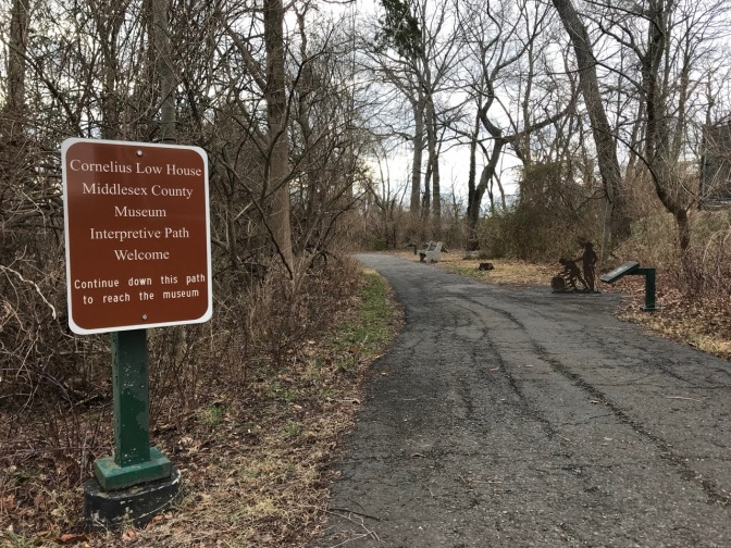 Path in woods. A sign beside it says CORNELIUS LOW HOUSE - MIDDLESEX COUNTY MUSEUM INTERPRETIVE PATH WELCOME CONTINUE DOWN THIS PATH TO REACH THE MUSEUM