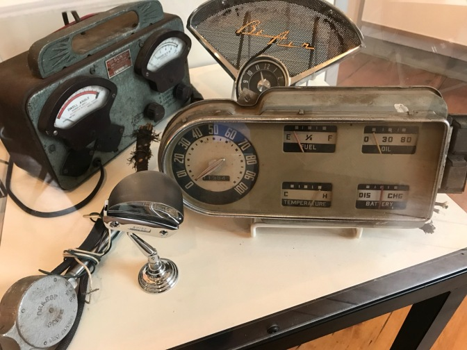 Display with gauge panel from 1951 Ford F-1 pickup, add-on turn signal indicator, Chevy Bel Air dashboard clock and speaker bezel, and Sun Dwell Tachometer.