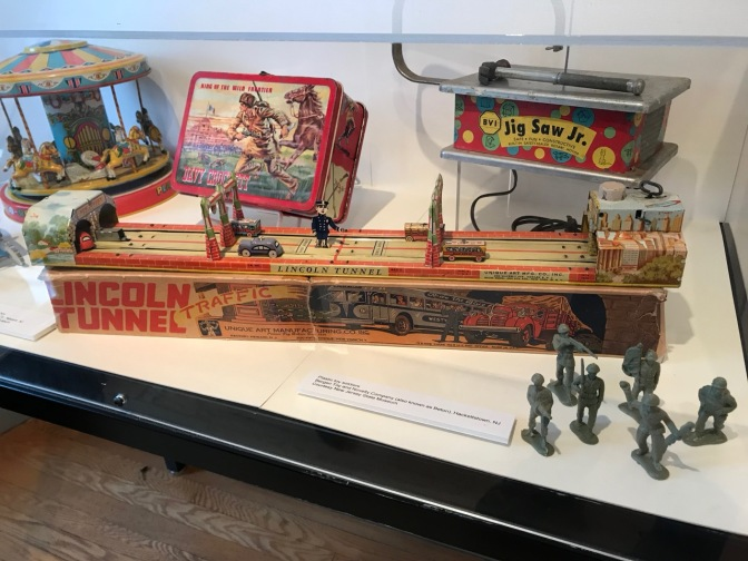 Display of 1950's toys including Lincoln Tunnel model car toy, a luncbox, a carousel, and a toy jig saw.