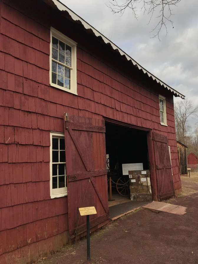 Exterior of blacksmith shop, painted red, with white window trim.
