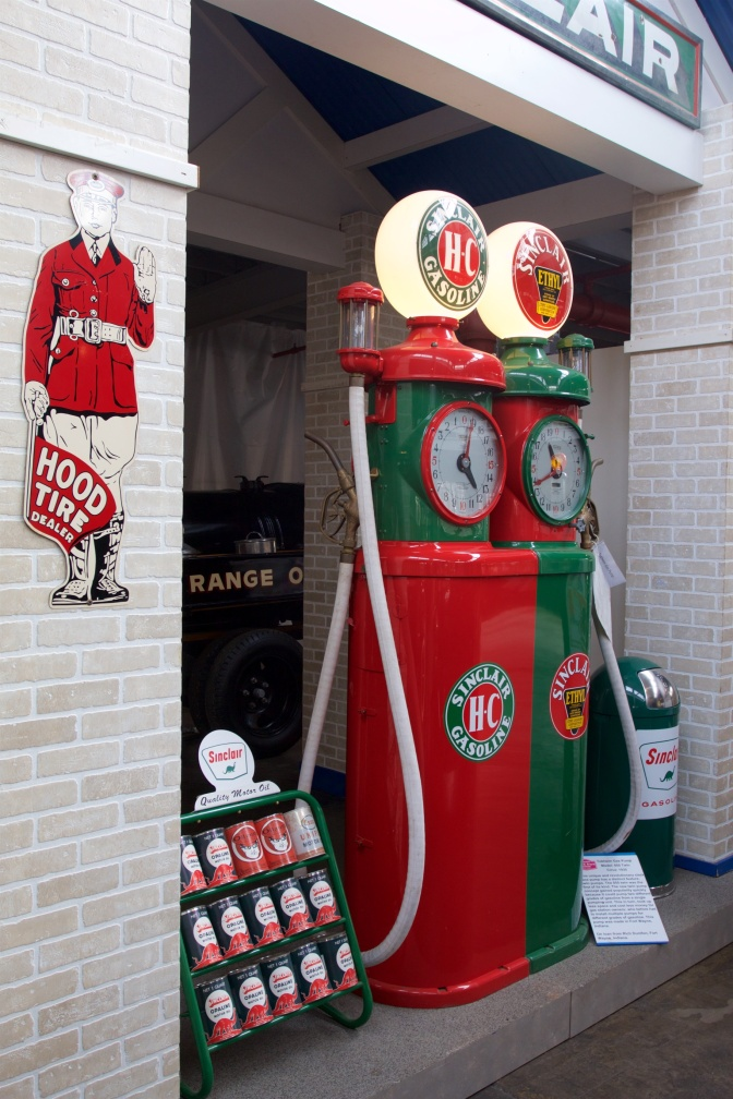 Two antique gasoline pumps, one in red, the other in green.