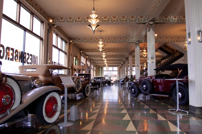 Showroom of old Duesenberg car dealership with classic cars on floor.