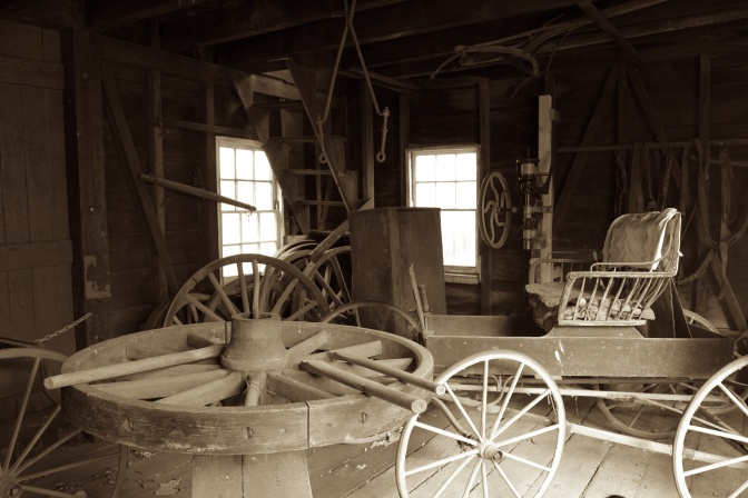 Wooden wheel being constructed in wheelwright shop, and a carriage is in the background.