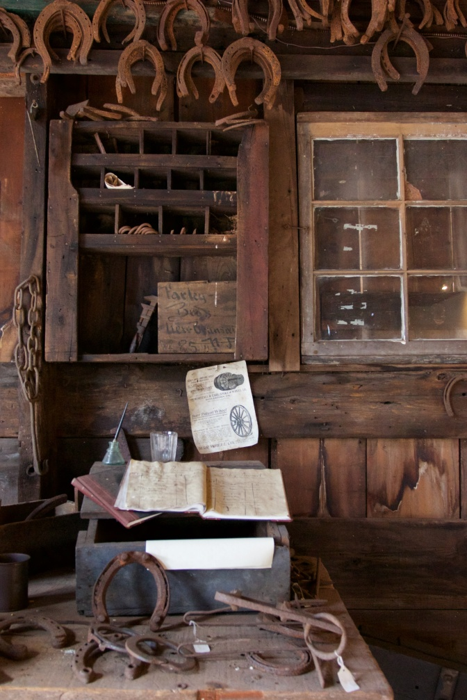 Interior of blacksmith shop. A table on foreground has ledgers and horseshoes. A cabinet with equipment is on the walls, and horseshoes hang from the ceiling.