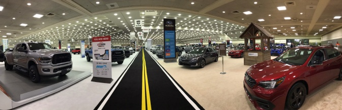 Panorama of interior of auto show, with the main pedestrian thoroughfare painted to look like a two-lane road.