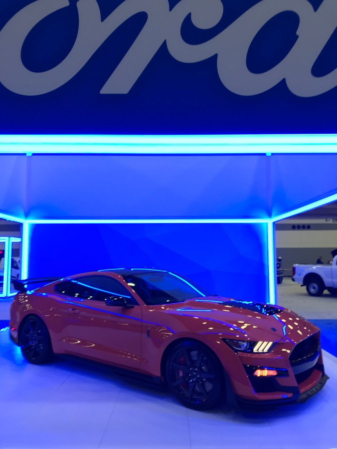 Red Ford Mustang coupe under blue awning.