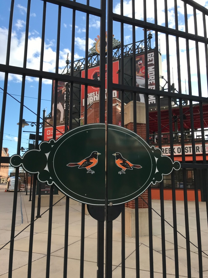 Gate with Orioles on latch of gate, with Camden Yards stadium in background.
